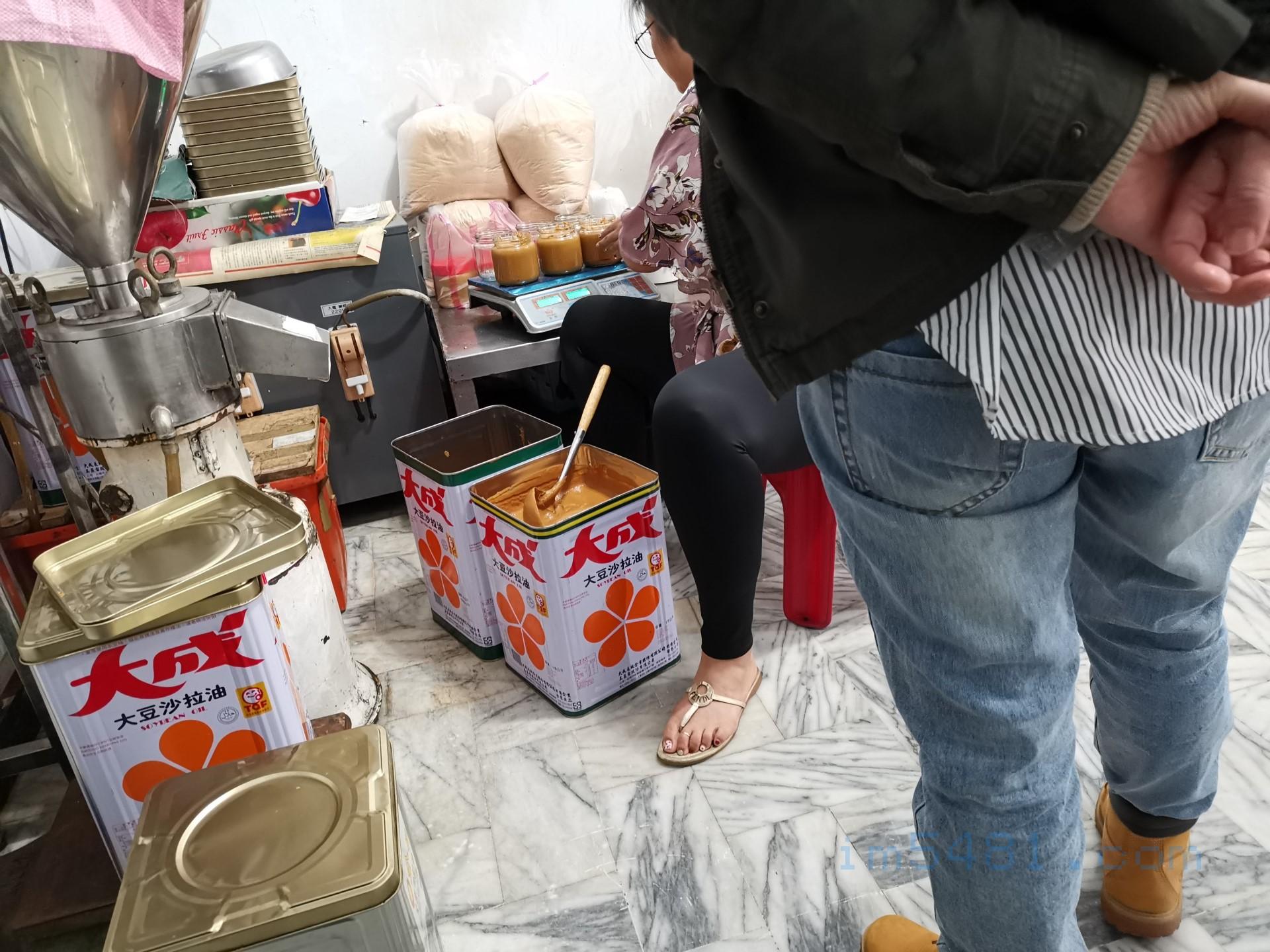 老闆女兒正幫忙裝客人的花生醬跟秤重