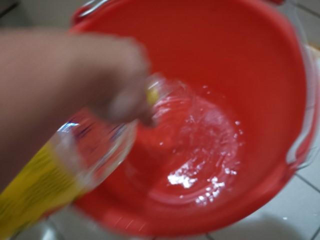 將準備稀釋的水倒進桶裡。建議醋酸水溶液濃度在浸泡衣服階段,最好約有酸度1%的醋酸濃度。