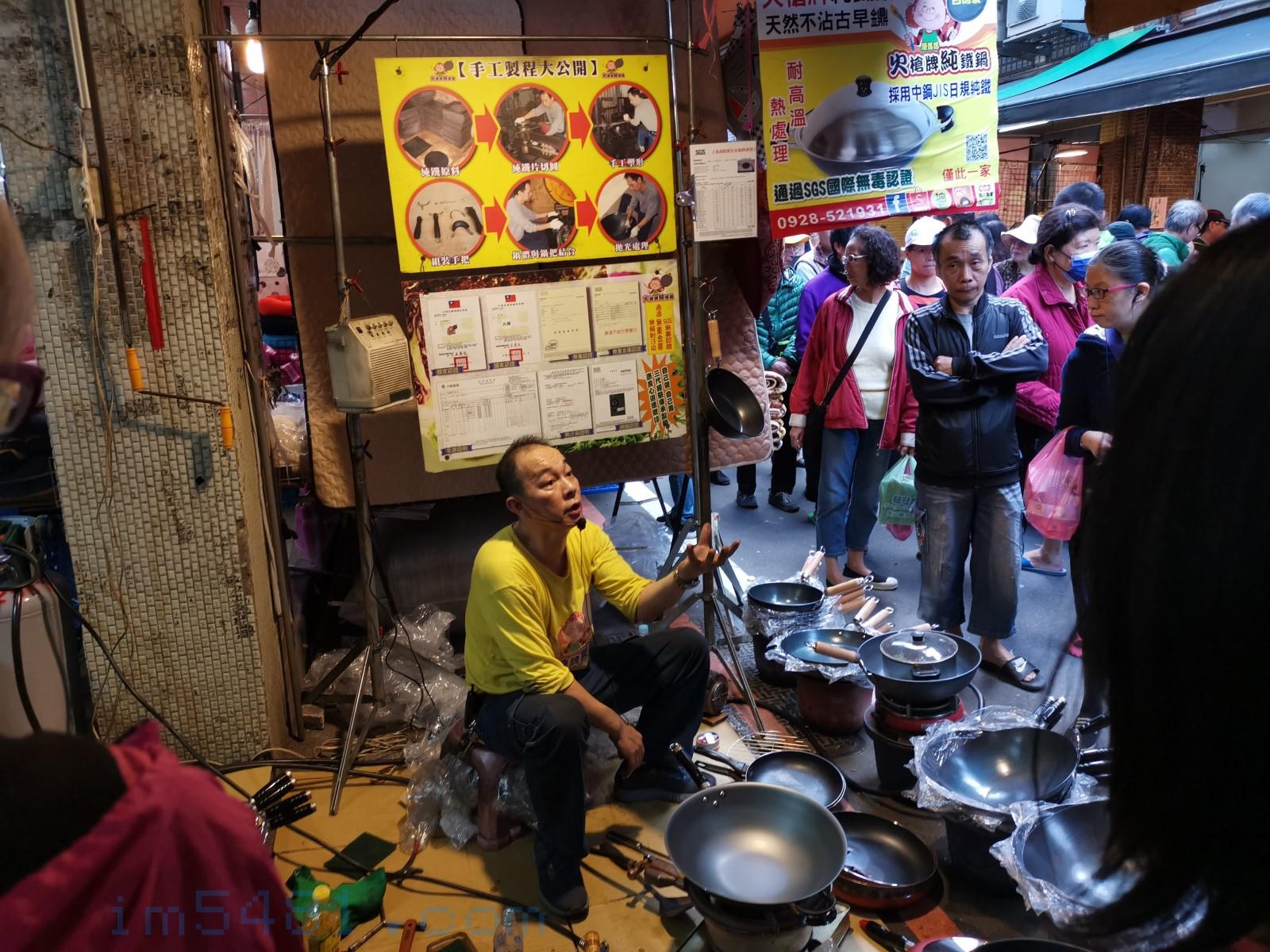火槍牌鐵鍋在七堵市場的攤位,老闆正在解說產品。