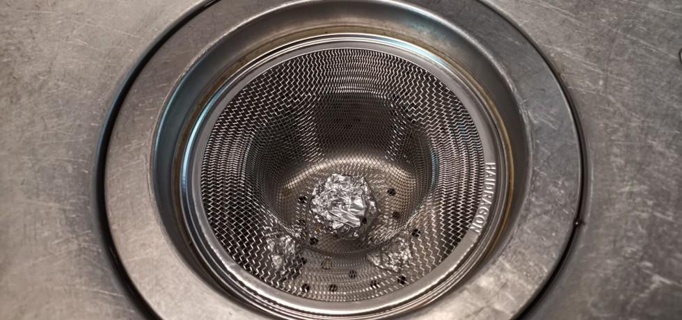 廚房水槽排水濾網上方放一個不鏽鋼濾網,並且在濾網上放上一顆圓形鋁箔球